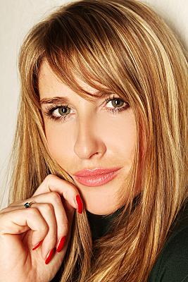 Portraitfoto junge, blonde Frau mit roten Nägeln.