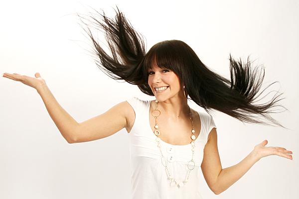 Portraitfoto einer jungen Frau mit wirbelndem langen, dunklen Haar im weißen Top.