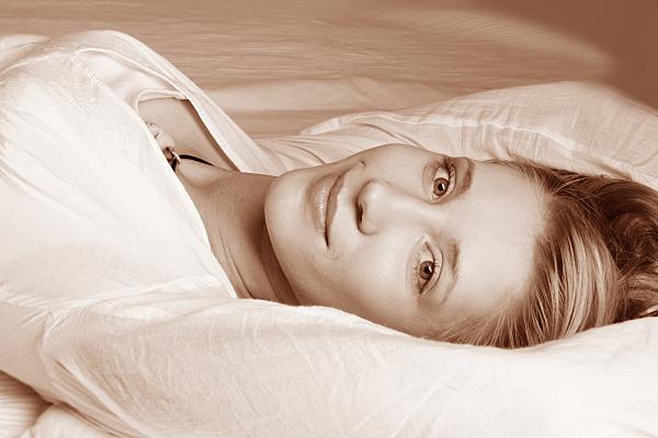 Portraitfoto einer liegenden, jungen Frau in weißer Bluse mit über den Kopf ausgestreckten Armen .
