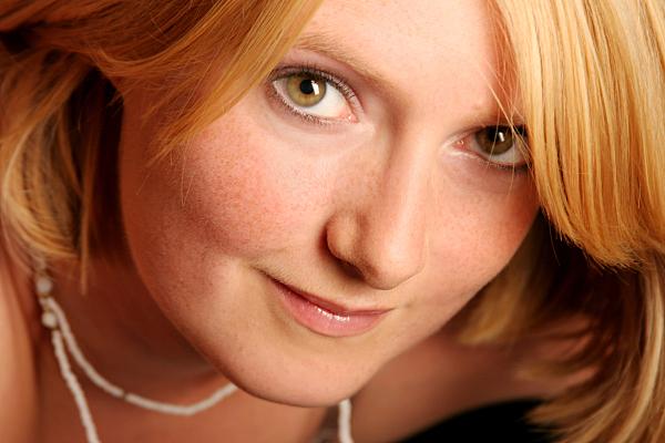Portraitfoto einer jungen Frau mit Sommersprossen und einer Perlenkette.