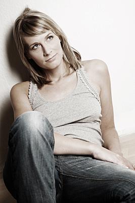 Portraitfoto einer jungen Frau, die verträumt nach oben schaut, im grauen Top vor einer cremeweißen Wand.