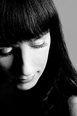Portraitfoto einer jungen, dunkelhaarigen Frau, die verträumt die Augen schließt und den Kopf Richtung Boden neigt.