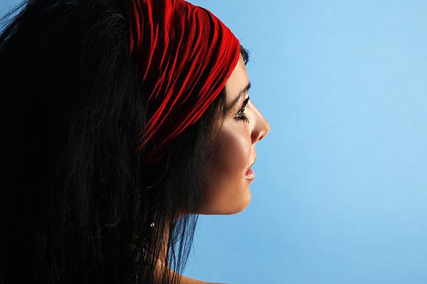 Portraitfoto einer jungen, dunkelhaarigen Frau mit roten Haarband vor einem hellblauen Hintergrund.