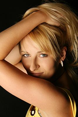 Portraitfoto einer jungen, blonden Frau, die verführerisch in die Kamera blickt und dabei ihre Haare nach oben aufgerafft hält.