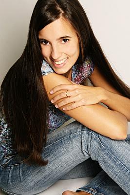 Portraitfoto einer jungen, dunkelhaarigen Frau, die freundlich in die Kamera lächelt und ihre Hand auf ihrem Oberarm abgelegt hat.