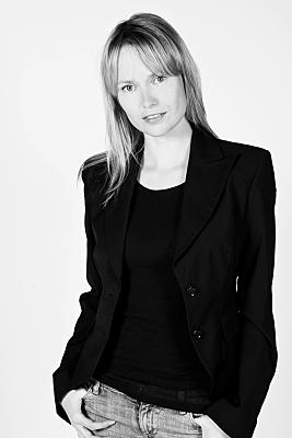 Schwarz-weißes Portraitfoto einer jungen Frau im Business-Look mit halblangen blonden Haaren und einem dunklen Blaser.