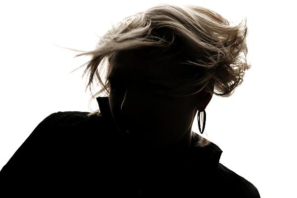 Schwarz-weißes Portraitfoto als Schattenspiel einer jungen Frau mit wirbelndem, kurzen blonden Haar und dunkler Bluse.