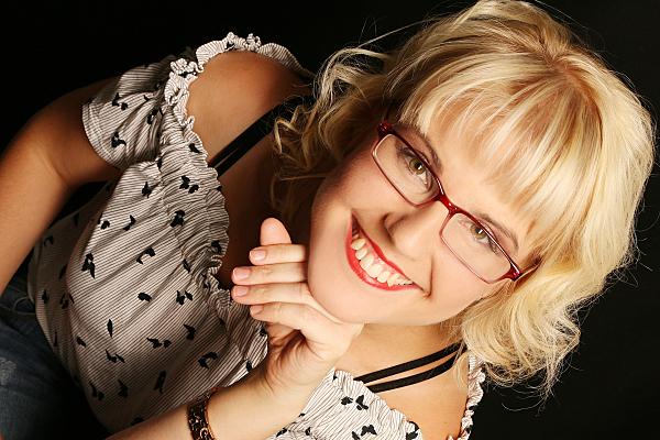 Portraitfoto einer jungen Frau mit blonder Kurzhaarfrisur, gepunkteter Brille und roter Brille, die lächelnd ihren Kopf auf die Hand stützt.