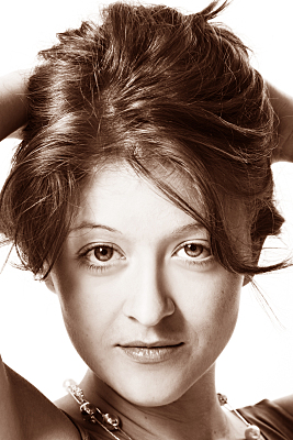Sepiafarbenes Portraitfoto einer jungen, brünetten Frau, die verträumt Richtung Boden blickt und dabei ihre Haare nach oben aufgerafft hält.