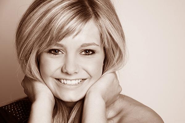 Sepiafarbenes Portraitfoto einer jungen, blonden Frau, die in die Kamera lächelt und dabei ihre Haare im Nacken zusammen hält.