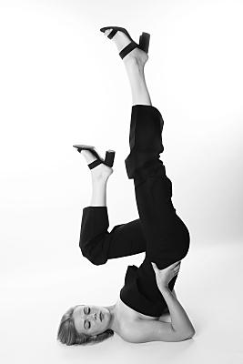 Schwarz-weißes Portraitfoto zweier Frauenbeine mit dunklen, hochhackigen Schuhen und dunkler Hose, die unterschiedlich hoch in die Luft gereckt sind.