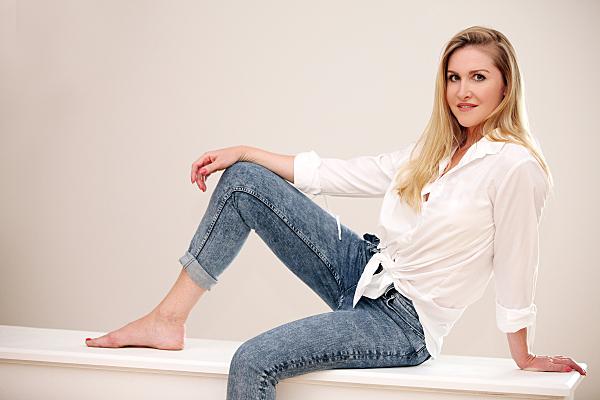 Portraitfoto einer jungen Frau mit langen blonden Haaren, Jeans und weißer Bluse, die auf einem weißen Quader mit angewinkeltem Bein sitzt und sich auf einem Arm abstützt.