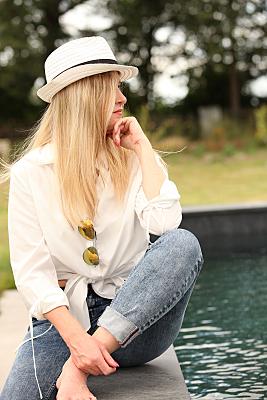 Portraitfoto einer jungen, verträumt ihre Hand am Kinn abgelegten, Frau mit langen blonden Haaren, weißer Bluse und weißem Hut mit Krempe vor einer Baumkulisse.