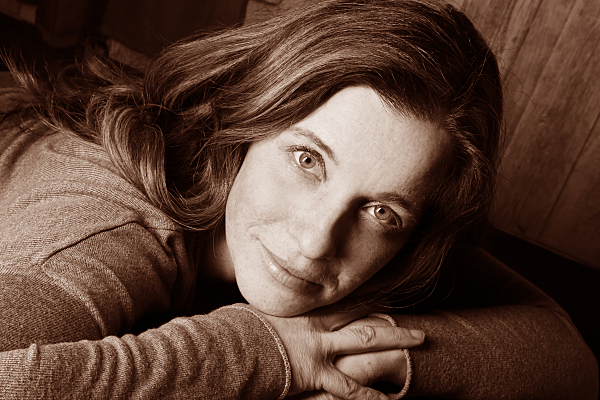 Sepiafarbenes Portraitfoto einer auf dem Bauch liegenden, jungen Frau mit brünetten Haaren, die ihr Gesicht auf den vor sich verschränkten Händen ablegt und verträumt in die Kamera blickt.