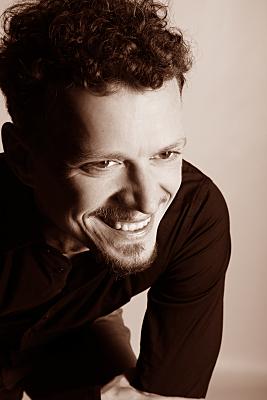 Dunkles, sepiafarbenes Portrait eines Mannes, aufgenommen von schräg oben, der offen lächelnd unter der Kamera durchschaut.