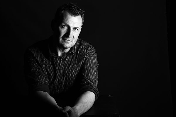 Low-Key schwarz-weiß Portrait eines Mannes vor schwarzem Hintergrund, der im rechten Teil des Bildes sitzt und neutral in die Kamera schaut.