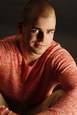 Kopfportrait eines Mannes mit rotem Pullover, der in die Kamera lächelt.