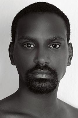 Kopfportrait eines dunkelhäutigen Mannes, frontal, der neutral in die Kamera blickt.