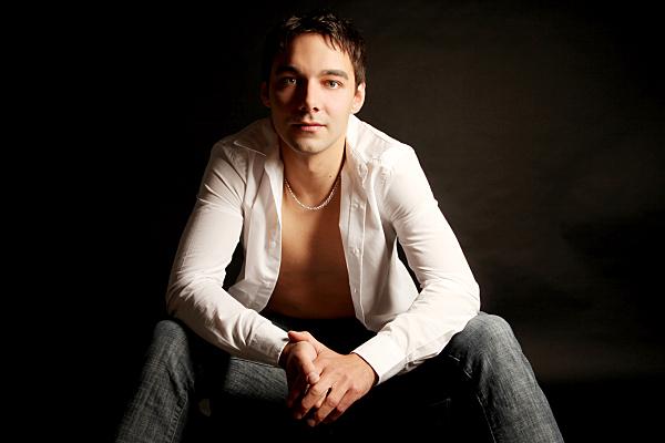Ganzkörperportrait eines Mannes mit offenem weißem Hemd, der sitzend, nach vorn auf seinen Knien abstützend in die Kamera schaut.