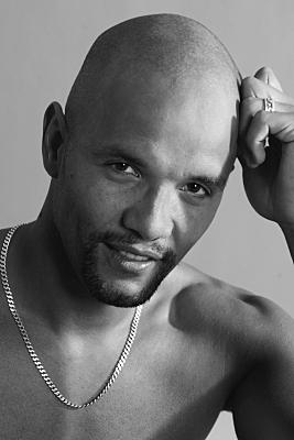 Schwarz-weiß Portrait eines oberkörperfreien Mannes, der seinen Kopf an die linke Hand lehnt und in die Kameralinse blickt.