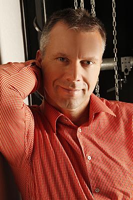 Portraitaufnahme eines Mannes mit rotem Hemd, der seine rechte Hand hinter seinen Kopf hält und geradezu leicht in die Kamera lächelt.