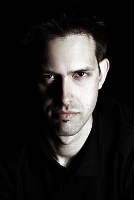 Low-Key Portraitaufnahme eines Mannes, der frontal in die Kamera schaut.