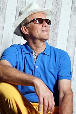 Portrait eines Mannes mit weißem Hut, blauem Poloshirt und gelber Hose, der nach schräg oben ins Licht schaut, von unten aufgenommen.