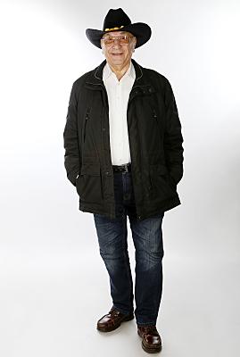 Ganzkörperporträt eines älteren Mannes mit Krempenhut und getönter Brille.