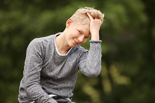 Portrait eines jungen Mannes, im Freien aufgenommen, der sich durch die Haare streift und dabei hinter der Hand in die Kamera lächelt.