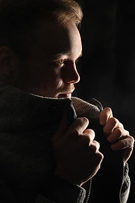 Low-Key Portrait eines Mannes, von der Seite aufgenommen, der seine offene Jacke mit beiden Händen am Kragen hält.