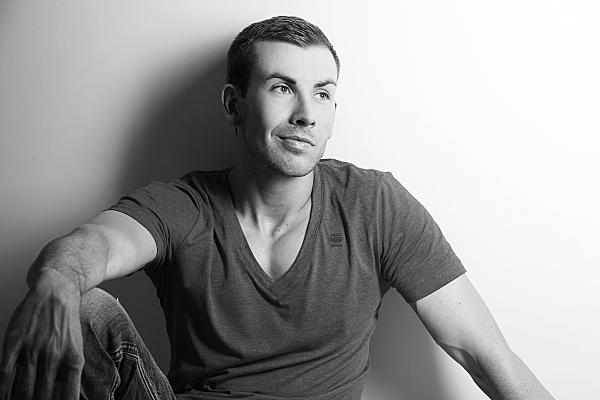 Schwarz-weißes Portrait eines Mannes, der sitzend an einer Wand lehnend in die Ferne blickt.