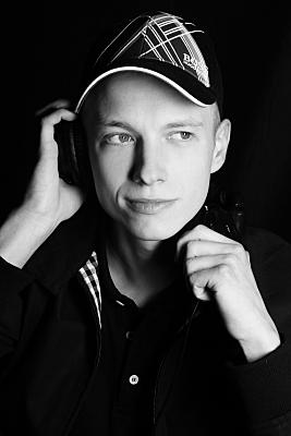 Nahportrait eines Mannes mit Cap, der sich einen Kopfhörer ans rechte Ohr hält und an der Kamera vorbei blickt.