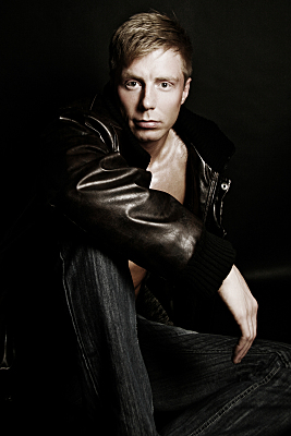 Low-Key Portrait eines Mannes, der über den Ärmel seiner Lederjacke in die Linse schaut.