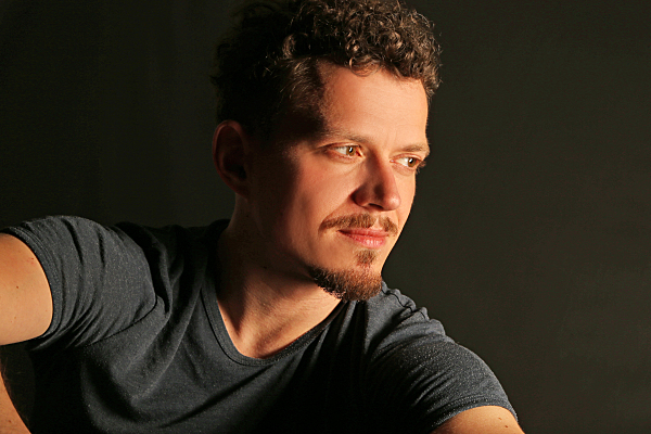 Portrait eines Mannes vor dunklem Hintergrund, der an der Kamera vorbei in die Ferne blickt.