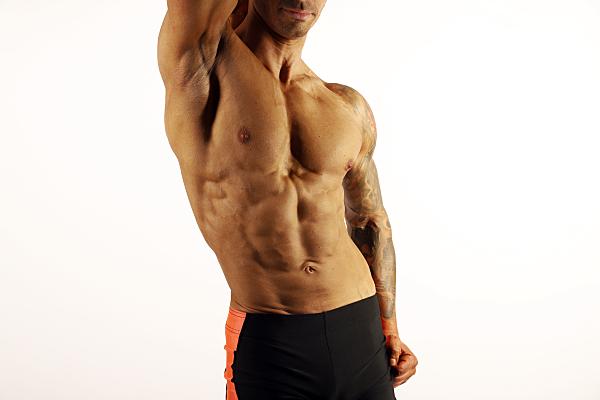 Sportfoto eines muskulösen Mannes mit nacktem Oberkörper und dunkler Sporthose vor einem hellen Hintergrund, der seinen einen Arm angewinkelt über den Kopf hält.