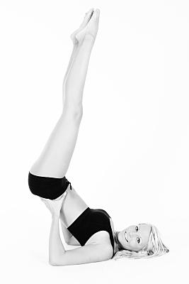 Schwarz-weißes Sportfoto einer Frau mit dunkler Unterwäsche, die auf einem Bein stehend, die ihre Beine zur Kerze in die Luft reckt und dabei freundlich in die Kamera lächelt.