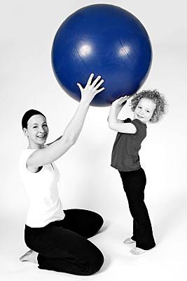 Sportfoto einer knienden Mutter in weißem Top und dunkler Sporthose, die gemeinsam mit ihrer Tochter einen blauen Ball über ihren Köpfen hebt.