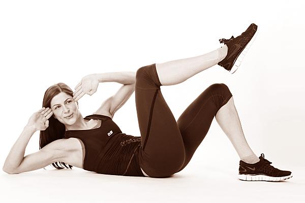 Sportfoto einer schlanken, dunkelhaarigen Frau beim Sit-up, die eine dunkle Sporthose und Top trägt, die Hände an den Kopf hält, ein Bein aufstellt und ein Bein in die Luft reckt.