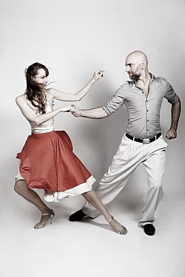 Sportfoto eines tanzenden Paares, das sich an den Händen hält und sich einander zudreht. Die Tänzerin trägt einen wirbelnden, roten Rock und ein geblümtes Oberteil, der Mann graues Hemd und helle Hose