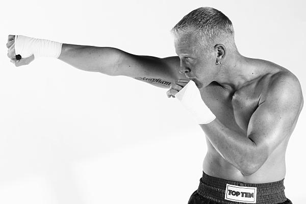 Sportfoto eines muskulösen Mannes mit nacktem Oberkörper und in schwarzer Sporthose, der eine bandagierte Hand ans Kinn hält, während er die andere zum Schlag streckt.