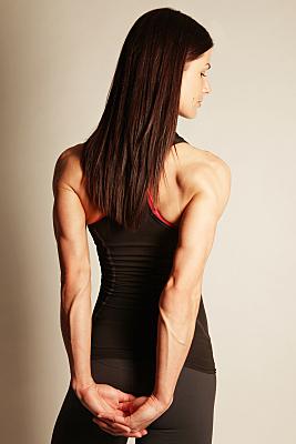 Sportfoto einer durchtrainierten Frau mit wehendem, langen dunklen Haar mit Tanktop in Rückansicht.