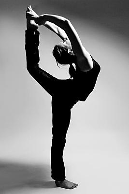 Schwarz-weißes Sportfoto einer Frau mit dunklem Top und dunkler Hose im Profil, die auf einem Bein stehend, ihr anderes Bein über den Kopf reckt und mit der Hand umschlossen hält.