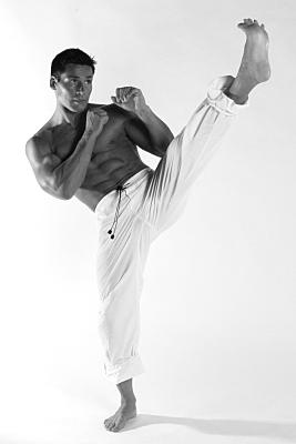 Sportfoto eines muskulösen Mannes mit nacktem Oberkörper und in weißer Sporthose, der die Arme in Boxpose hält und ein Bein nach oben kickt.