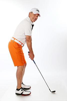Sportfoto eines älteren Mannes in weißem Hemd, weißem Cap und oranger Hose mit weißem Gürtel und einem Golfschläger in der Hand.