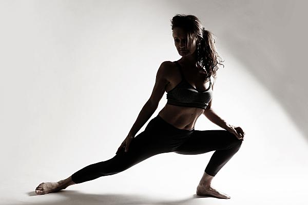 Schwarz-weißes Silhouetten-Sportfoto einer nackten Frau mit Zopf in Yoga-Krieger-Pose vor einem hellem Hintergrund.