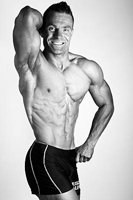 Sportfoto eines muskulösen Mannes mit nacktem Oberkörper, der seinen einen Oberarm über den Kopf streckt und dabei in die Kamera lächelt.