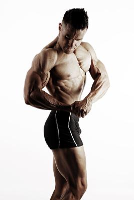 Sportfoto eines muskulösen Mannes mit nacktem Oberkörper, der seinen Oberarm anwinkelt und auf seine starken Muskeln hinabschaut.