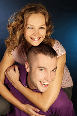 Portrait eines jungen, fröhlichen Paares, aus einer leichten Vogelperspektive, auf dem der Mann die Frau auf dem Rücken trägt und beide in die Kamera lächeln.