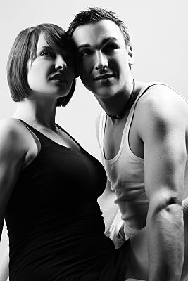 High-Key Portrait eines Paares von schräg unten aufgenommen, auf dem beide die Köpfe aneinander lehnen und schräg über die Kamera hinweg in die Ferne blicken