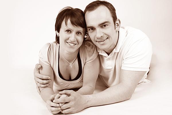 High-Key Portrait eines Paares, das nah beieinander auf dem Boden liegend in die Kamera schaut.